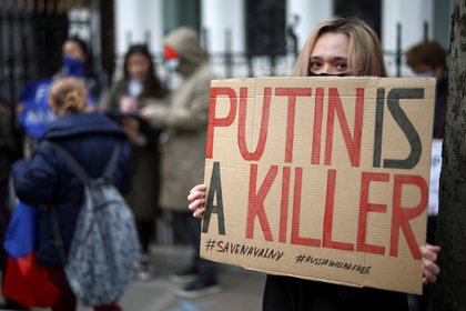 A woman holds a poster as she participates in a rally in support of imprisoned Russian opposition politician Alexei Navalny in front of the Russian Embassy in London, Britain, on April 21, 2021. Reuters