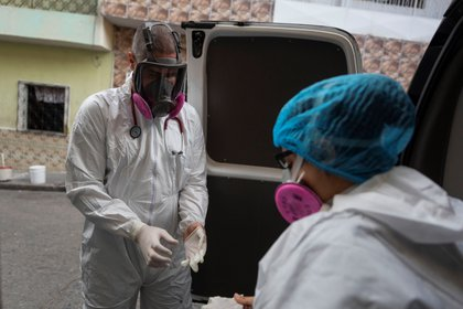 The paramedics of Angels de los Viaz, Jolly Rodr (guez (d) and Jonathan Quantip (i) are preparing to treat a patient with COVID-19 at home on April 22 in Caracas (Venezuela).  EFE / Reiner pen r.