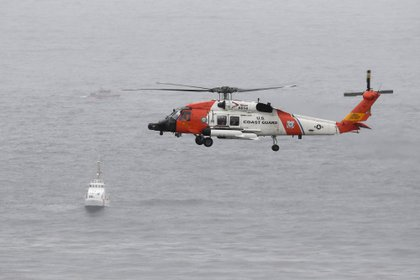 A U.S. Coast Guard helicopter flies over ships searching the wreckage area of a ship off the coast of San Diego Sunday.  (AP Photo / Denise Borai)