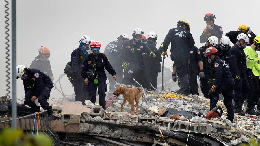 Firefighters remove their dead 7-year-old daughter from the rubble of a Miami building