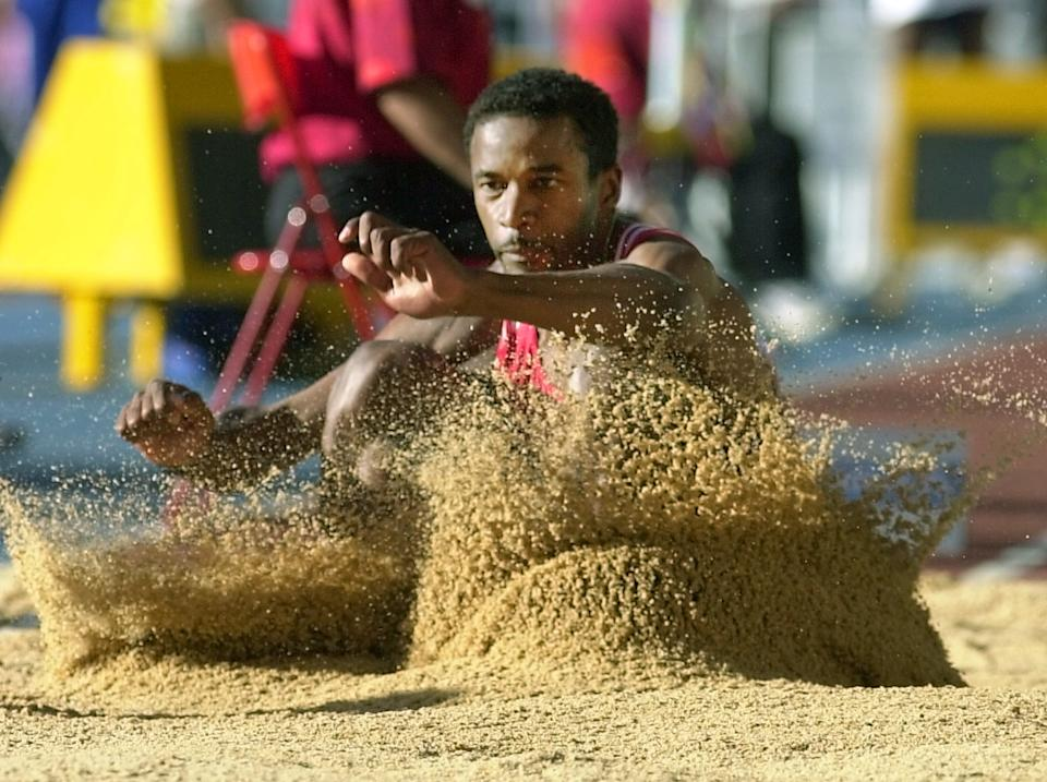 Cuban Ivan Pedroso plunges into the sand during the men's long jump qualifying round at the World Championships in Athletics in Seville on August 26, 1999 (Photo by Eric Feverberg/AFP) (Photo by Eric Feverberg/AFP via Getty Images)